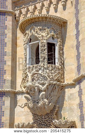 Sculpture of a mythological triton that symbolizes the allegory of creation of the world. Detail on facade of Pena National Palace, Unesco Heritage in Sintra, Portugal.