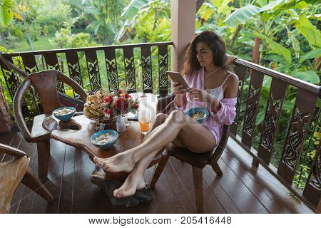 Young Woman Use Cell Smart Phone While Breakfast On Terrace In Tropical Garden Beautiful Girl Messaging Online Eating Oatmeal With Fruits In Morning