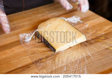 Piece of cheese in cling film on wooden table background, copy space, closeup