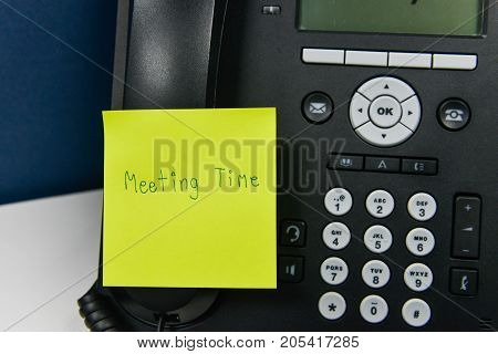 Paper note with meeting time wording is sticked on the IP Phone