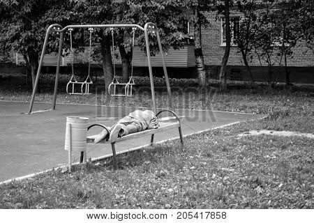 The homeless man sleeps on a bench in the playground. Refugees. Monochrome image