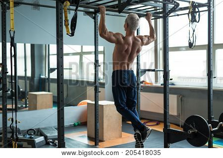 Muscular athlete man making Pull-up in gym. Bodybuilder training in fitness club showing his perfect back and shoulder muscles