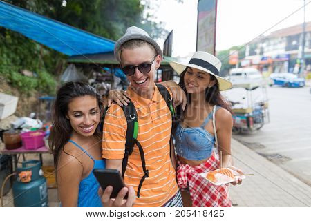 Group Of Tourists Use Mobile Phone To Find Rigt Direction Or For Selfie Photo While Walking Street Of Asian City Together On Vacation In Asia