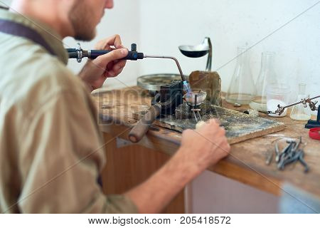 Back view of young man holding small gas torch and melting tools while working with metal at shabby wooden workstation