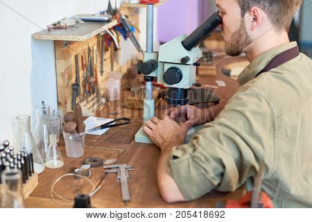 Portrait of young man inspecting precious stones using microscope sitting at workshop table