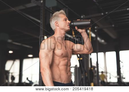 Young muscular man showing his perfect body. Man drinking from a cocktail shaker with the protein. Toned image.