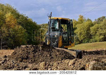 A bulldozer pushes dirt at a rural countryside construction site.