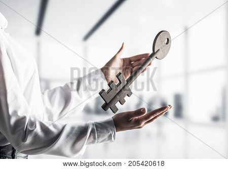 Business woman in white shirt keeping big stone key in hands with office view on background. Mixed media.