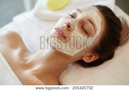 Closeup portrait of blissful young woman enjoying beauty treatments and face masks in SPA, lying on massage table with eyes closed