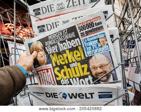 PARIS FRANCE - SEP 23 2017: Man buying latest newspaper Die Bild with with portrait of Angela Merkel And Martin Schulz before the election in Germany for the Chancellor of Germany the head of the federal government currently Angela Merkel