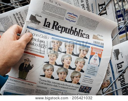 PARIS FRANCE - SEP 23 2017: Man buying latest Italian La Republica newspaper from press kiosk with Braking news from Theresa May British Prime Minister Brexit news and multiple faces