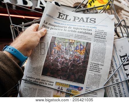 PARIS FRANCE - SEP 23 2017: Man buying latest Spanish El Pais newspaper as Pro referendum supporters are seen holding placards during a protest a week before the final vote for the independence of Catalonia