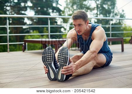 Confident young sportsman sitting on wooden floor of spacious terrace and doing stretching exercises before intensive workout, picturesque view on background