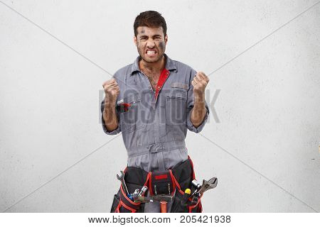 Indoor Shot Of Annoyed Electrician Can`t Reconstruct Doorbell, Look Nervously, Link Angrily Teeth, C