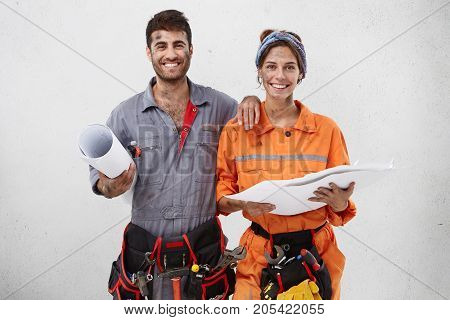 Pleased Content Female And Male Manual Workers Hold Sketch, Look And Plan Their Work For Next Week,