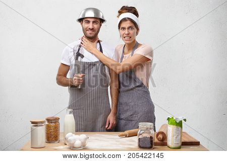 Indoor Shot Of Irritated Housewife Being Busy As Cooking, Argues With Husband Who Is Lazy Bone, Keep