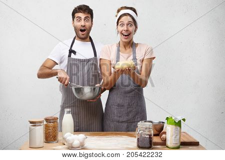 Astonished Male Anf Female Cookers Look With Jaw Dropped Out And Widely Opened Eyes, Make Pastry For
