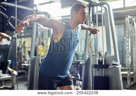 Young sporty man using cable crossover machine while having intensive workout, interior of modern gym on background