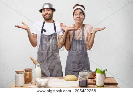 Uncertain Woman And Man Wears Aprons, Shrug Shoulders With Hesitation, Don`t Know How To Cook Flaky