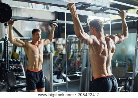 Handsome young bodybuilder with bare torso doing exercises for biceps in front of mirror while having intensive workout at modern gym