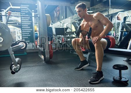 Pensive sporty man sitting on bench at spacious gym and having intensive training with dumbbells, full length portrait