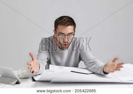Troublesome Male Designer Have Problems With Project, Looks Nervously At Drawings, Gestures With Han