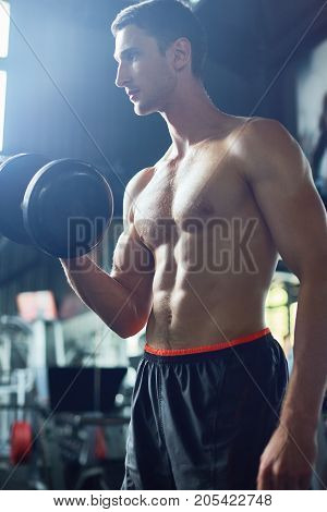 Portrait of handsome young bodybuilder with bare muscular torso looking away pensively while working out with dumbbells, blurred background