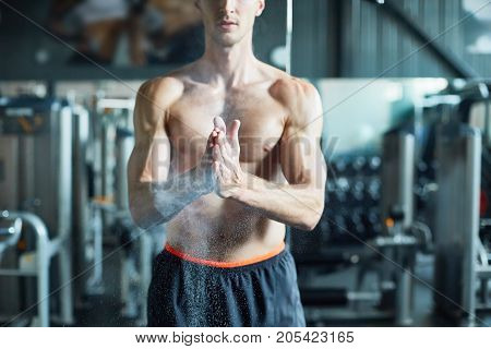 Cropped image of unrecognizable young sportsman rubbing hands with chalk while preparing for doing exercise with barbell, blurred background