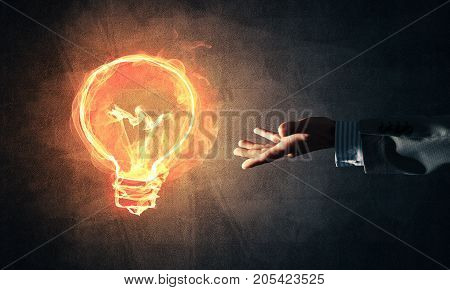 Close of businessman hand showing at glowing fire light bulb icon