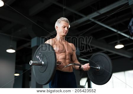 Strong man with muscular body working out in gym. Weight exercise with barbell in fitness club