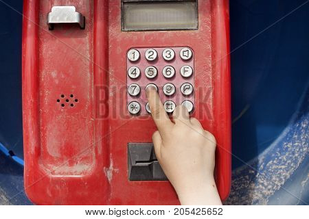 A small child's hand dials a phone number on a street phone. Protection of the rights of the child. Child abuse