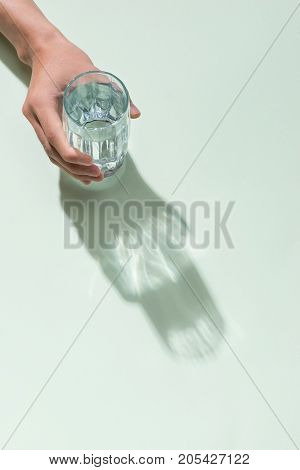 Hand holding a glass of water with back lighting