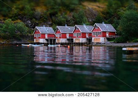 Small fish boat houses at Flam, Norway. Tilt shift effect. Classic red rorbu cabins near the river bank. Fisherman house