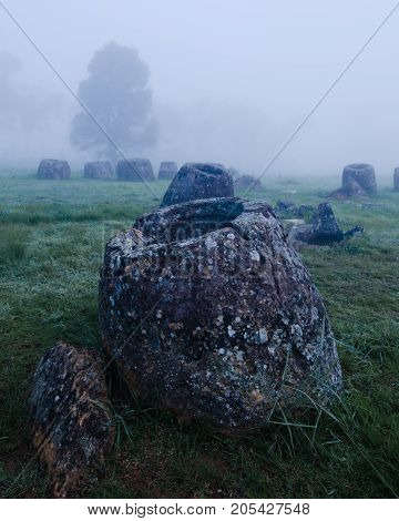 Amongst a field of landmines and bombs from the Vietnam war ancient jars are the last witnesses of a lost Laotian civilisation. The Plain of Jars near Phonsavan Laos is best seen at dawn.
