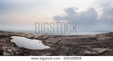 Barren rock and puddle. Panorama shot of the sunrise sky and its reflection in a puddle of water from the vantage point of Pidurangala rock next to the famous Sigiriya Lion Rock in Sri Lanka.
