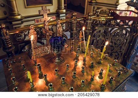 stand for candles in the interior of orthodox church golden candleholder in churchorthodox icon lamp church oil church attribute symbolic gold cross with the crucifixion of Jesus