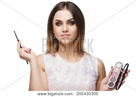 Beautiful Smiling Woman With A Brush For Makeup And Palette Of Eyeshadows In The Hands