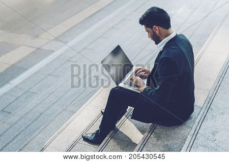 Handsome young manager working on laptop while sitting outdoors on the stairs concept of work life balance.