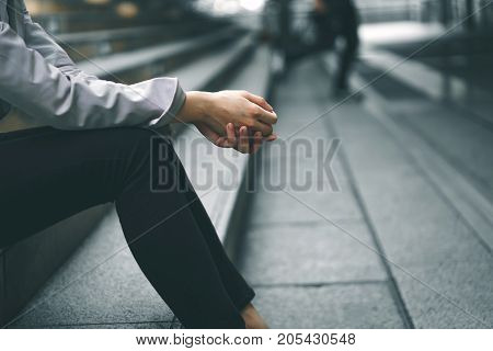Close-up hands of businesswoman stressed from work while sitting outdoors on the stairs concept work life balance burn out syndrome press from colleagues.