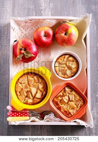 Apple puddings in small tins on tray overhead shot