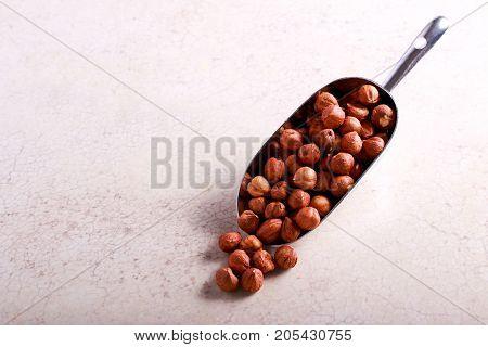 Hazelnuts in metal scoop on marble table