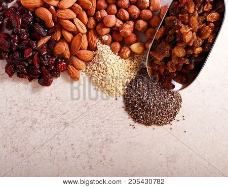 Nuts seeds cranberry and raisin on marble table