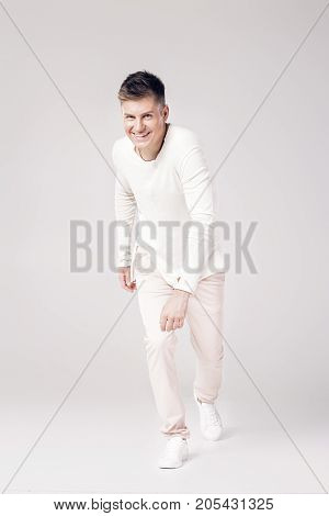 handsome smiling young man in a white sweater is ready to run forward. start