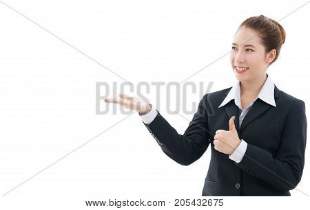 Young Asian businesswoman in black suit and white t-shirt opening her hand and giving the thumbs-up for concept placing a sign or object isolated on white background