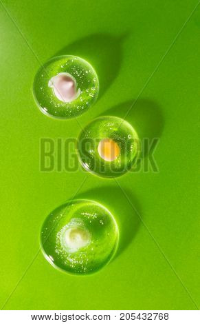 Three drops of cosmetic clear gel with various creams on a green background. The concept of biological compatibility of products with human skin