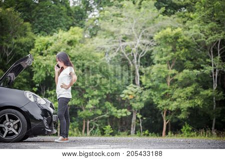 Broken down car and asian woman calling car mechanic