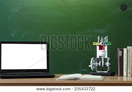 Teacher student on engineer desk table. Education background. Education concept. Laptop with blank screen copybook and education model of internal combustion engine on the table.
