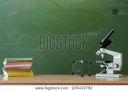 Teacher or student desk table. Education background. Education concept. Microscope and books on blackboard (chalkboard) background. Chemistry or biology lesson.