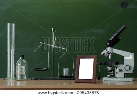 Teacher or student desk table. Education background. Education concept. Microscope beakers vials photo frame and scales on the table. Chemistry or biology lesson.