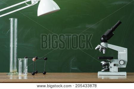 Teacher or student desk table. Education background. Education concept. Microscope flasks and molecule model on the table with lamp on blackboard (chalkboard) background. Chemistry or biology lesson.